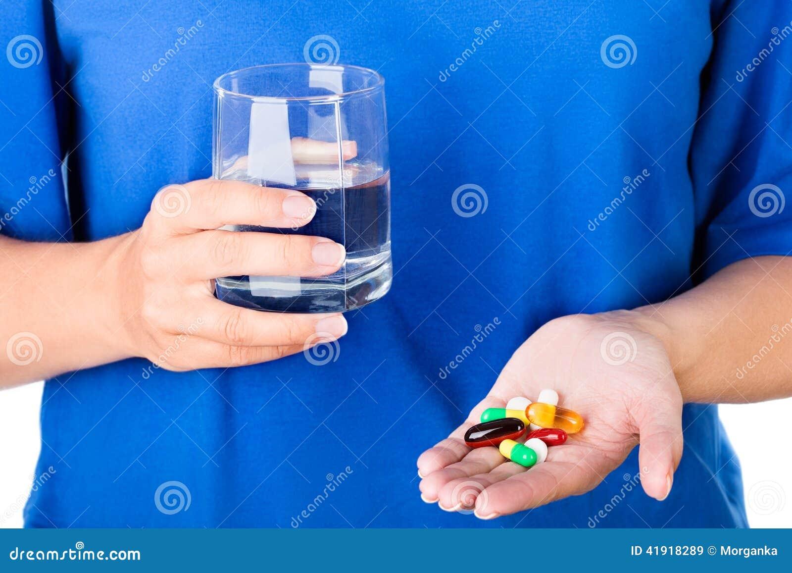Mujer que sostiene el vidrio de agua y el paquete de píldoras