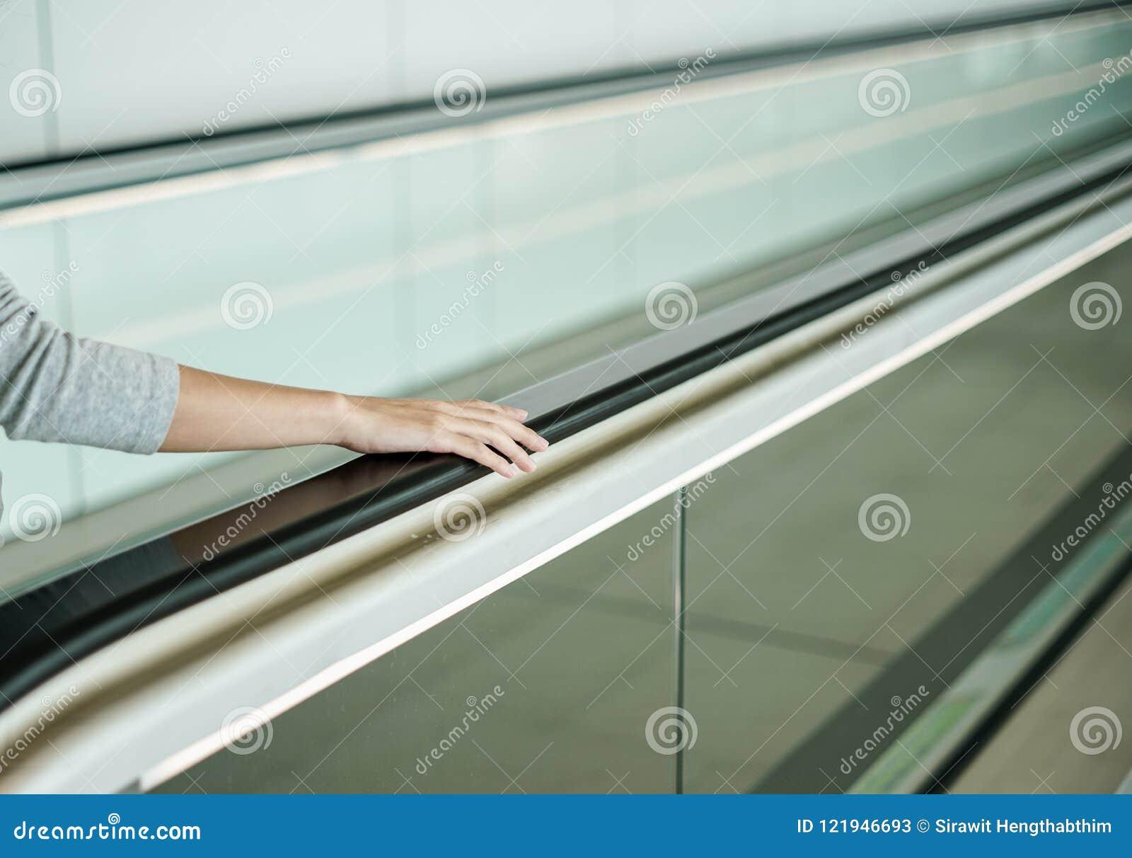 Mujer que sostiene encendido la barandilla cuando escalera móvil ascendente