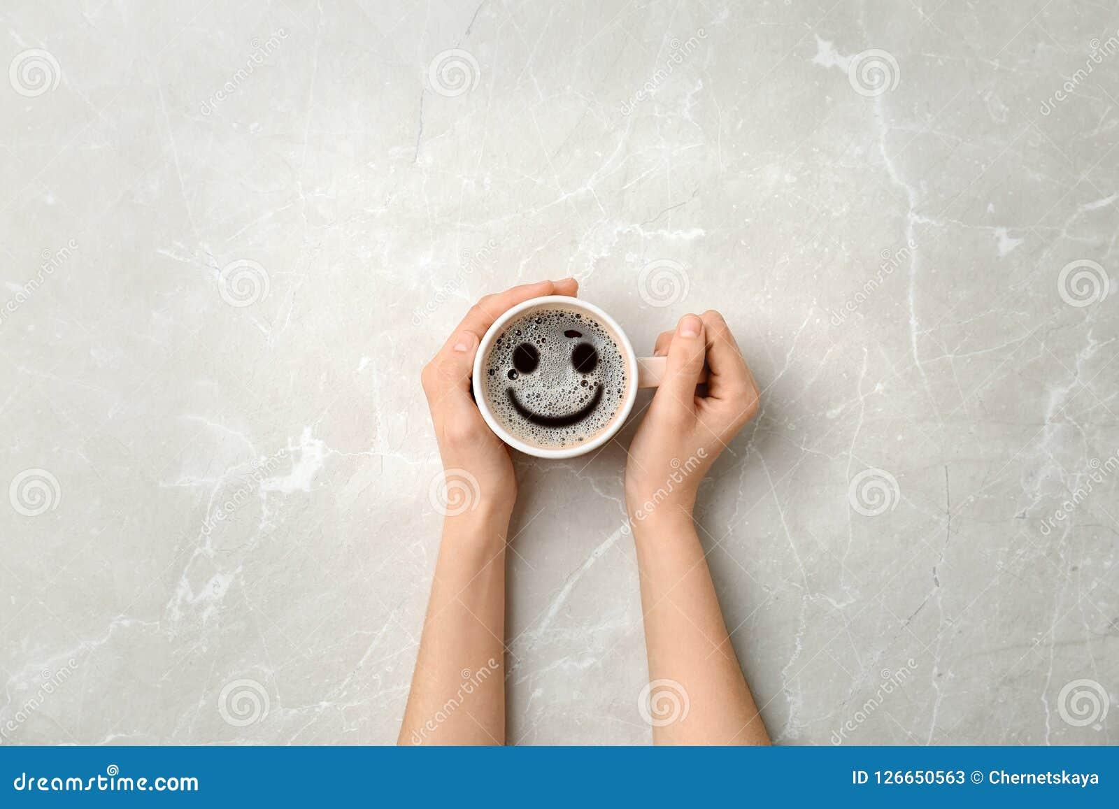 Mujer que sostiene la taza de café caliente delicioso con espuma y de sonrisa en el fondo ligero, visión superior Mañana feliz, b
