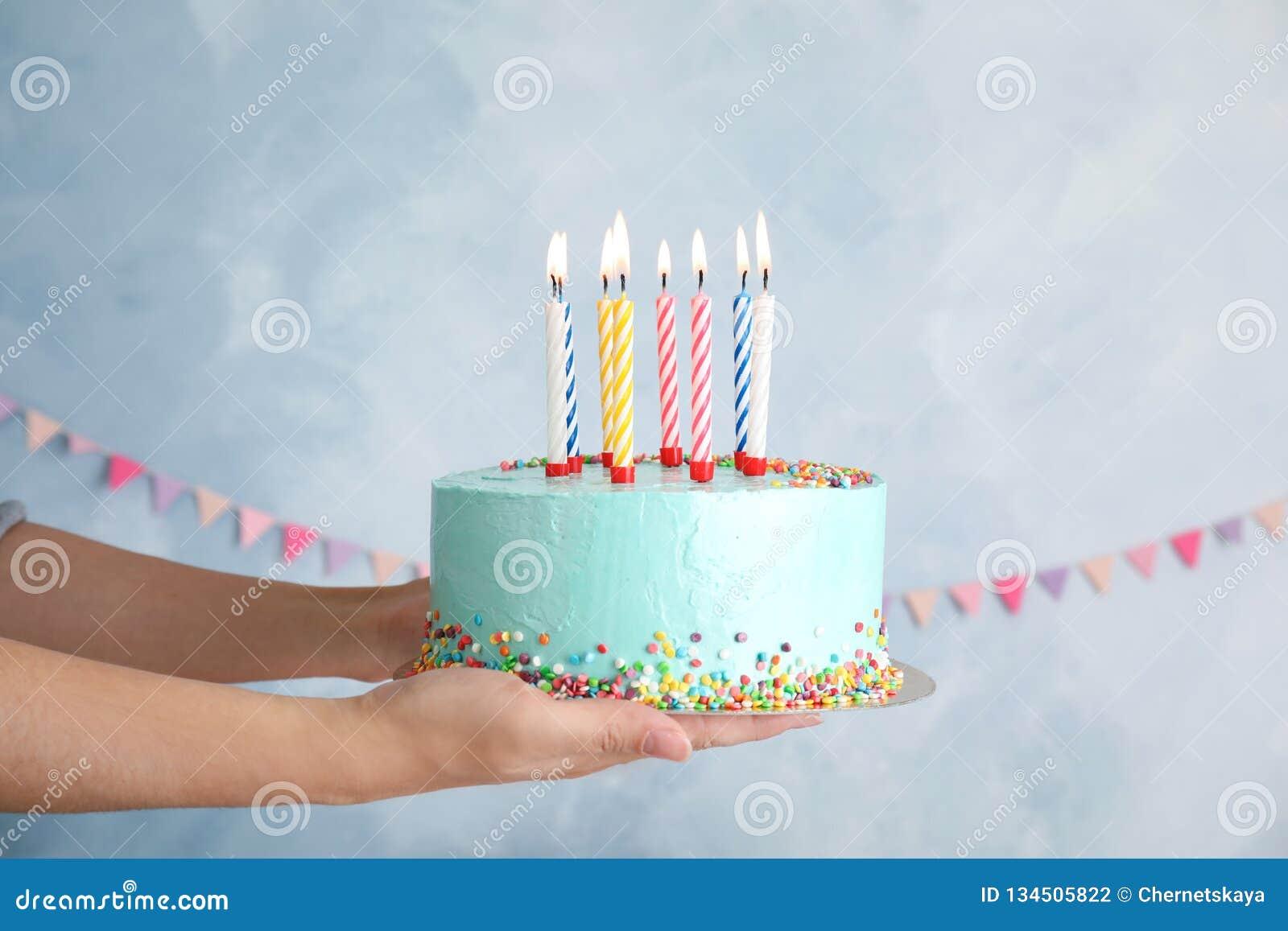 Mujer que sostiene la torta de cumpleaños deliciosa fresca con las velas