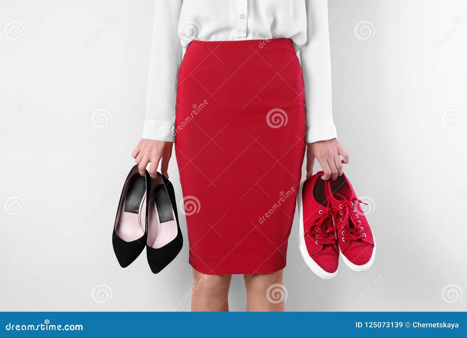 Mujer que sostiene los zapatos de tacón alto y las zapatillas de deporte en el fondo blanco, primer