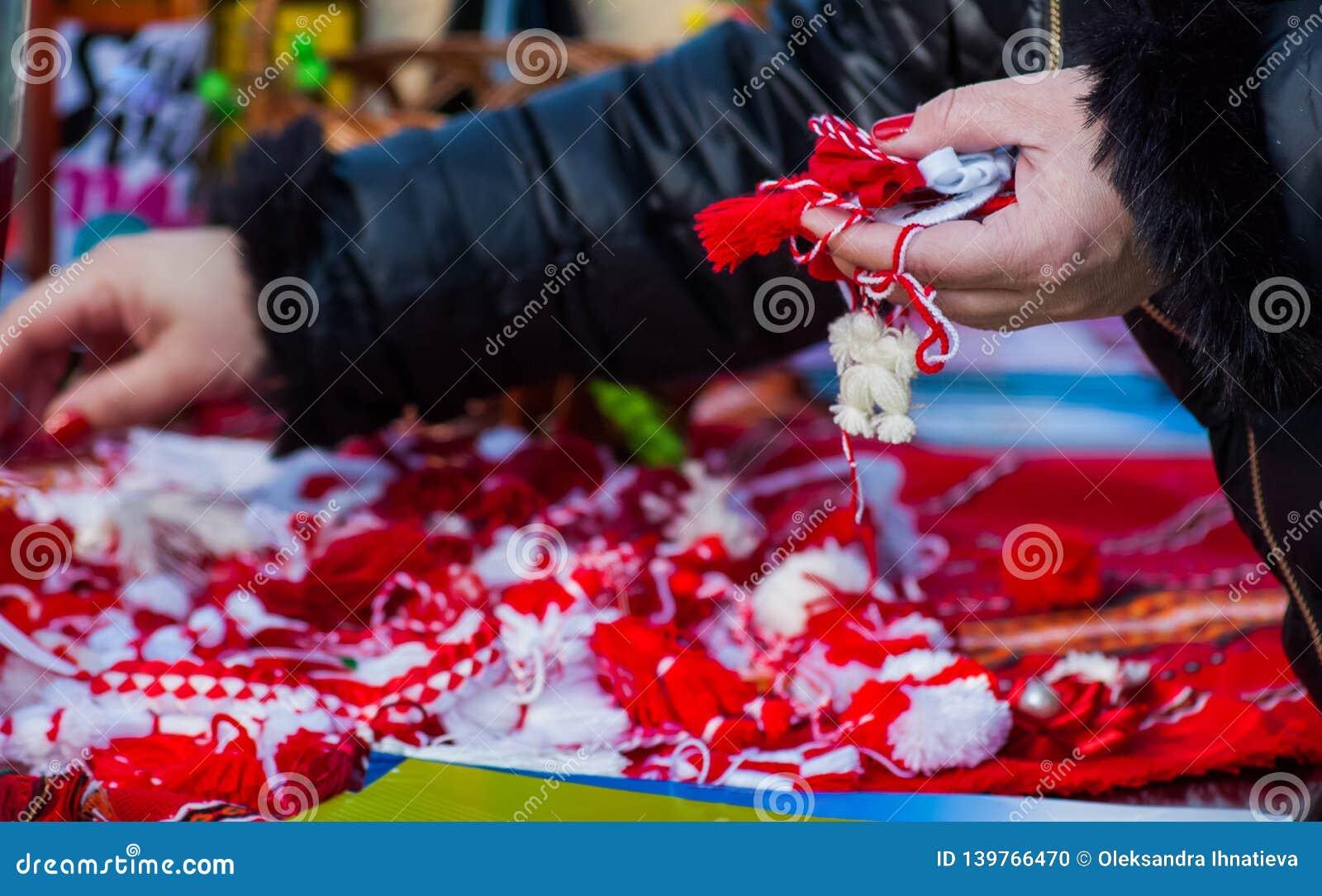Mujer que sostiene martisor y martenica tradicionales rojos y blancos en su mano al aire libre