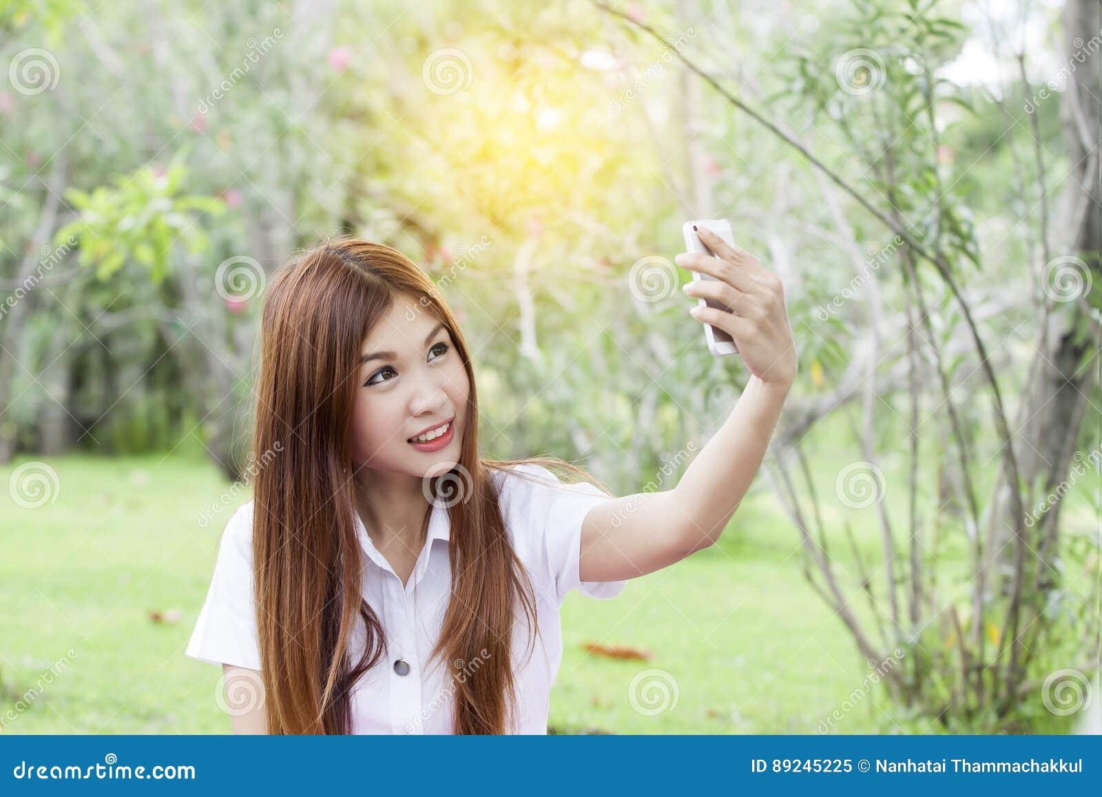 Mujer que sostiene su teléfono móvil y que toma el selfie
