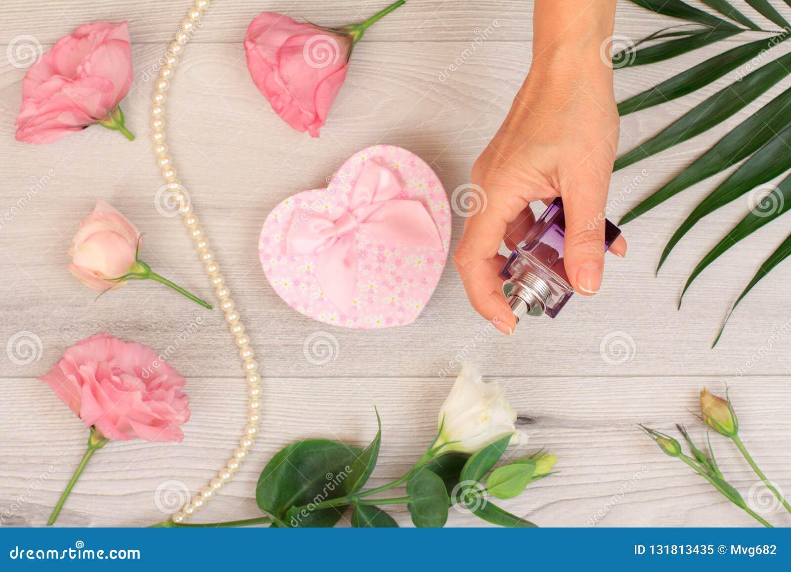Mujer que sostiene una botella de perfume en la mano con las flores en el fondo