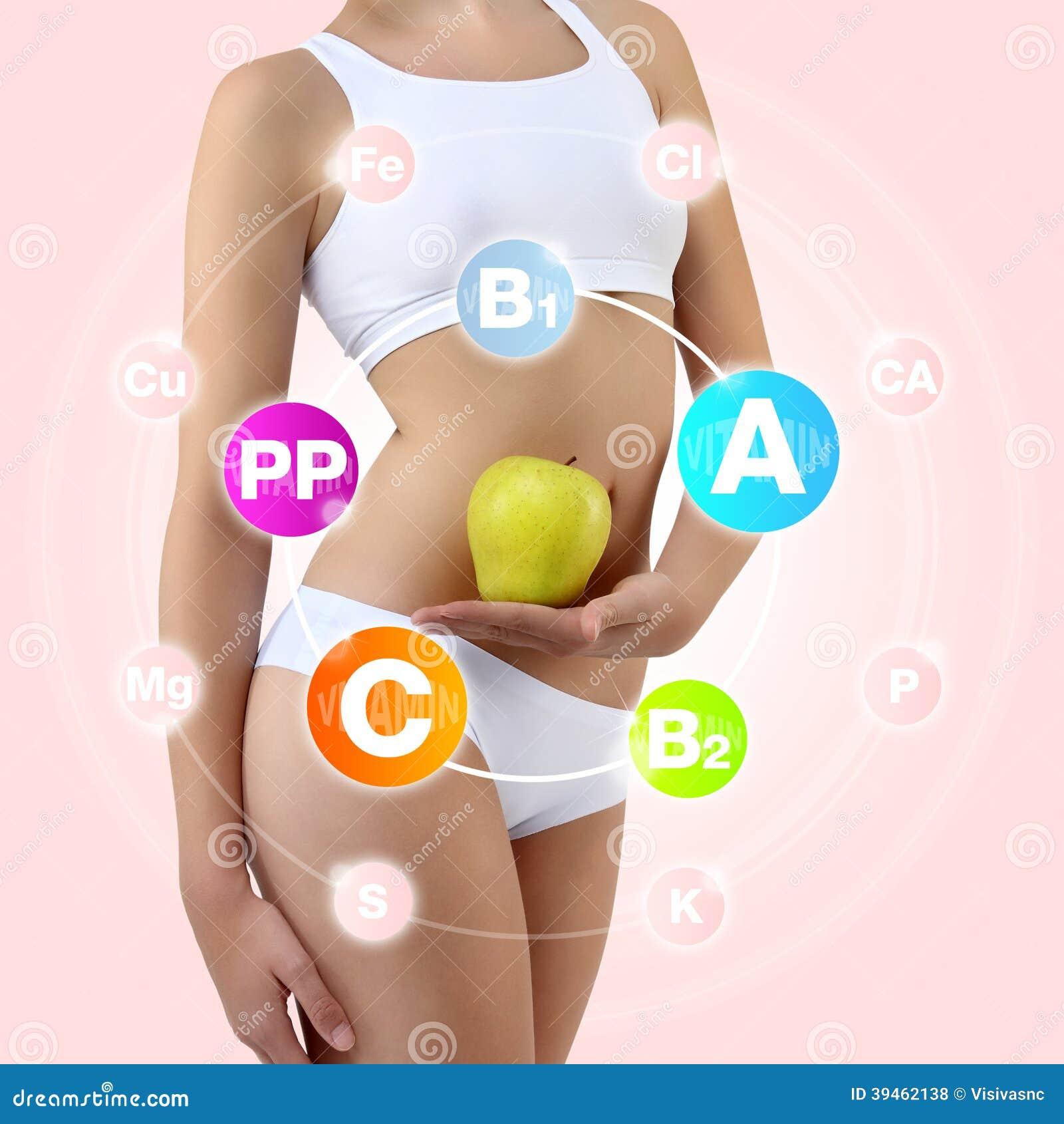 Mujer que sostiene una manzana y un melocotón con sus manos cerca del vientre