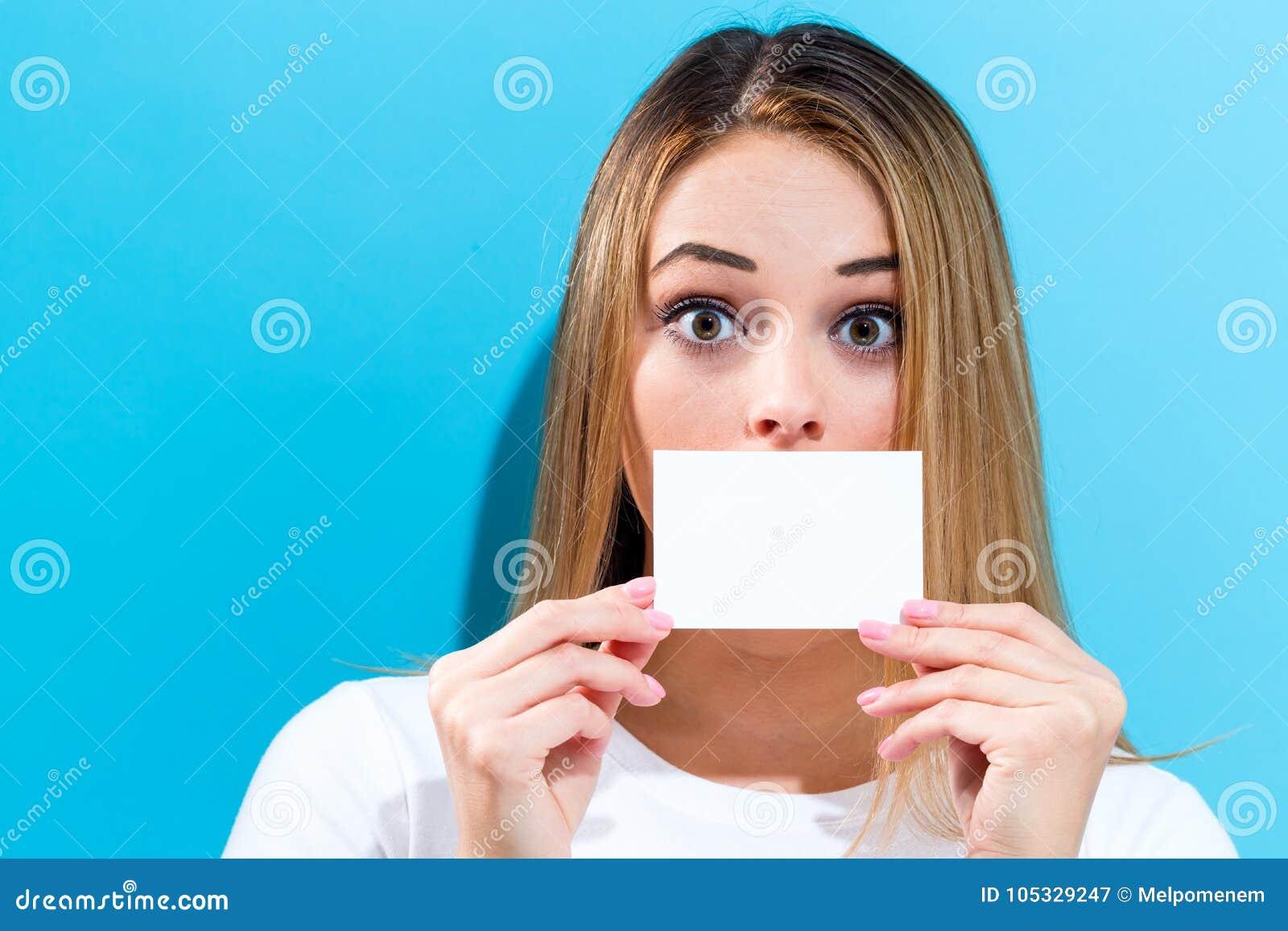 Mujer que sostiene una tarjeta en blanco del mensaje