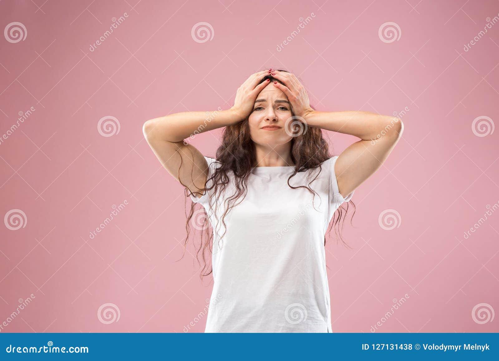 Mujer que tiene dolor de cabeza Aislado sobre fondo rosado