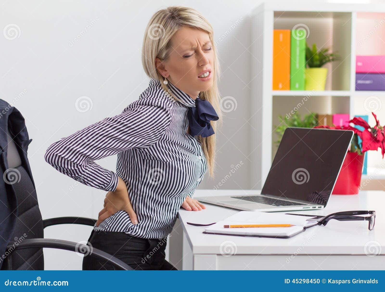 Mujer que tiene dolor de espalda mientras que se sienta en for Que tiene una oficina