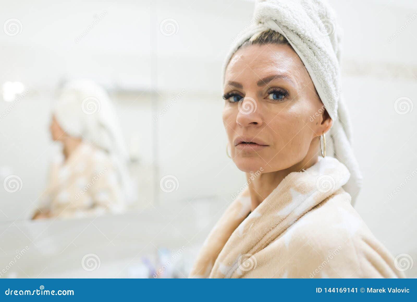 Mujer que tiene toalla en la cabeza después de tomar una ducha Mirada en cámara