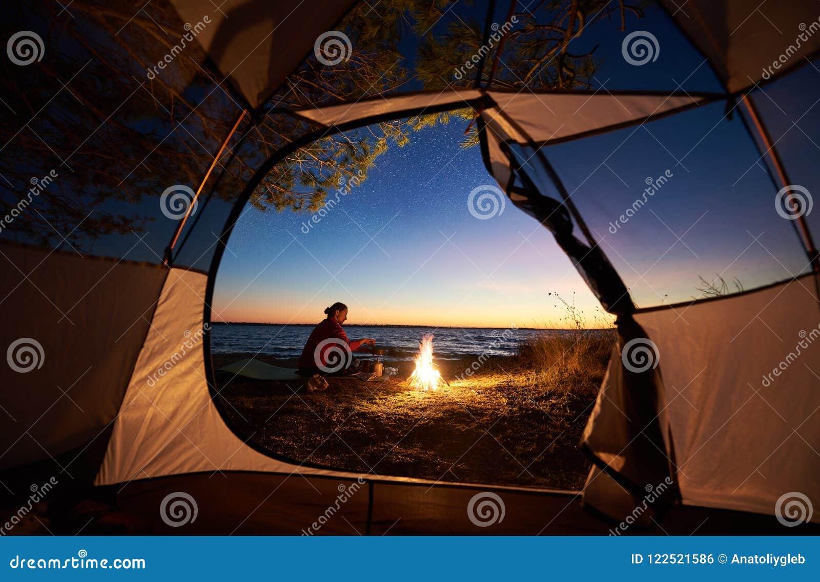 Mujer que tiene un resto en la noche que acampa cerca de la tienda turística, hoguera en orilla de mar debajo del cielo estrellad