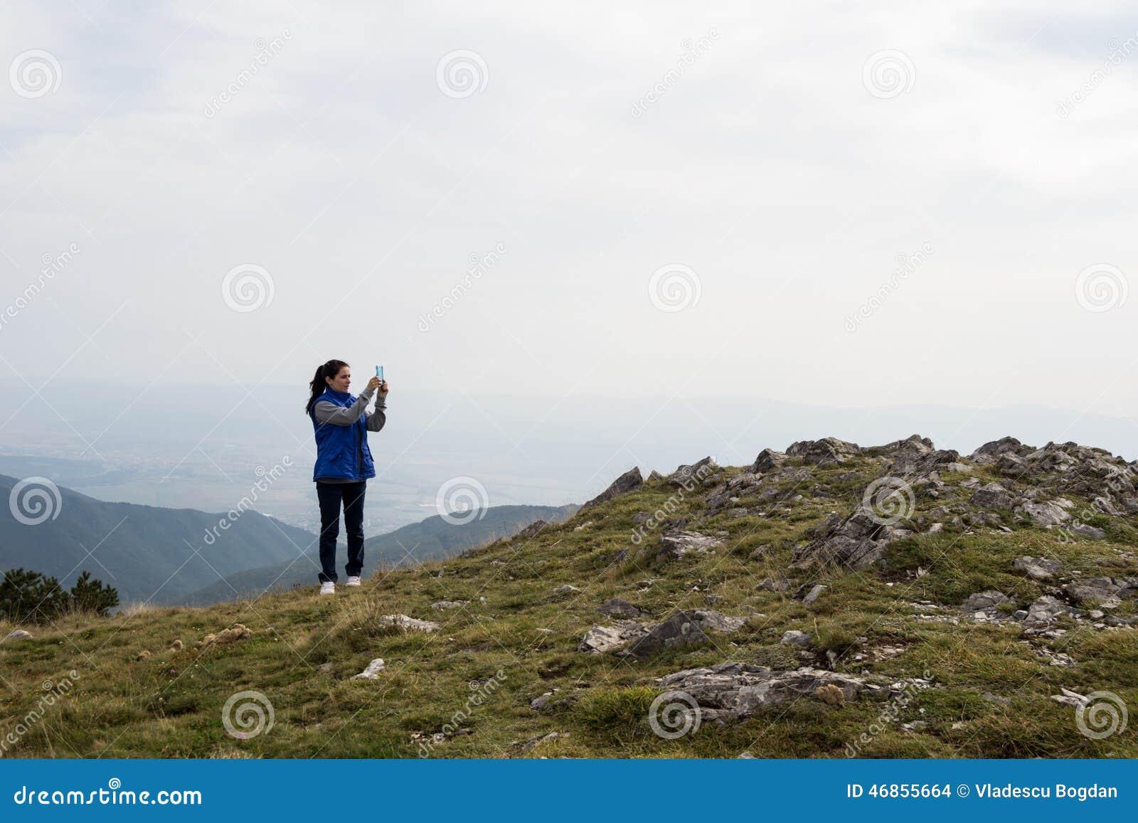 Mujer que toma la foto con el teléfono celular móvil