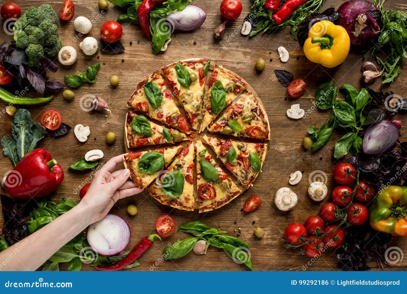 Mujer que toma la rebanada de pizza