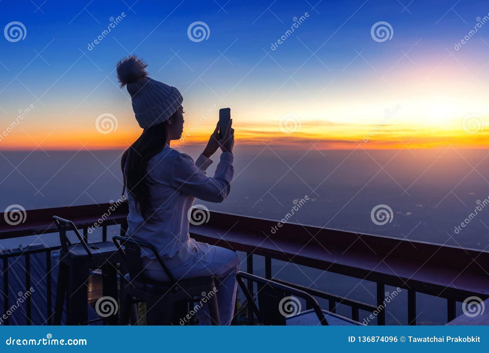 Mujer que toma las fotos de la salida del sol