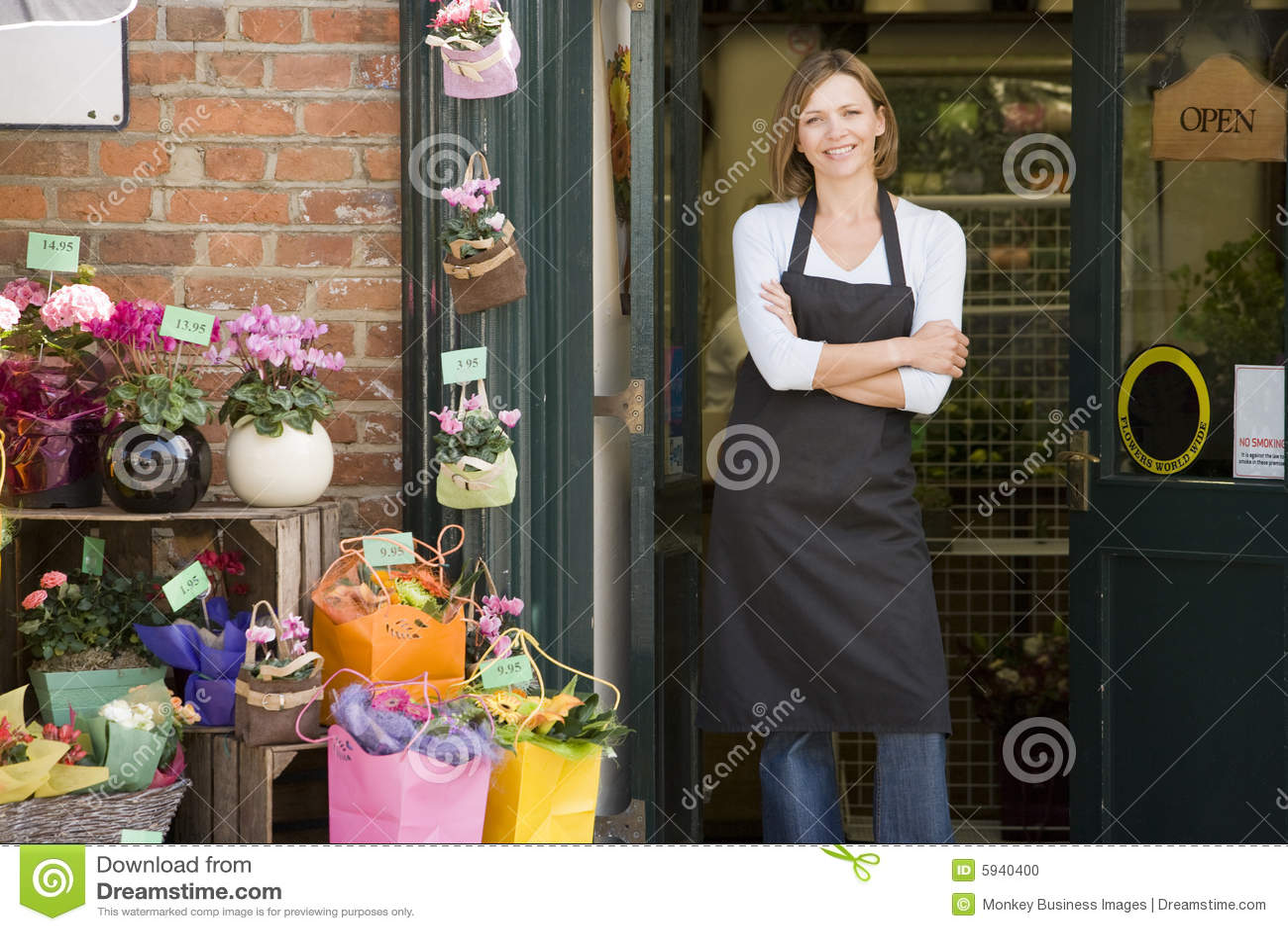 Mujer que trabaja en la sonrisa del departamento de flor