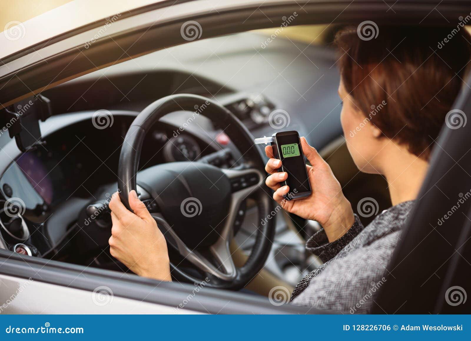 Mujer que usa el analizador del alcohol de la respiración en el coche