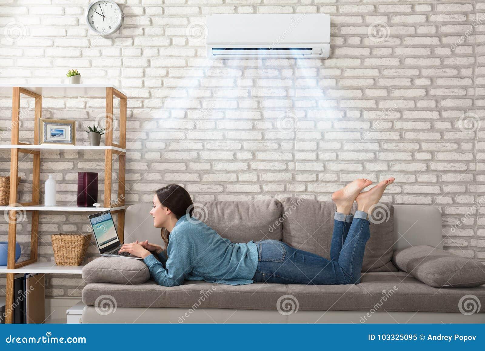 Mujer que usa el ordenador portátil debajo del acondicionador de aire