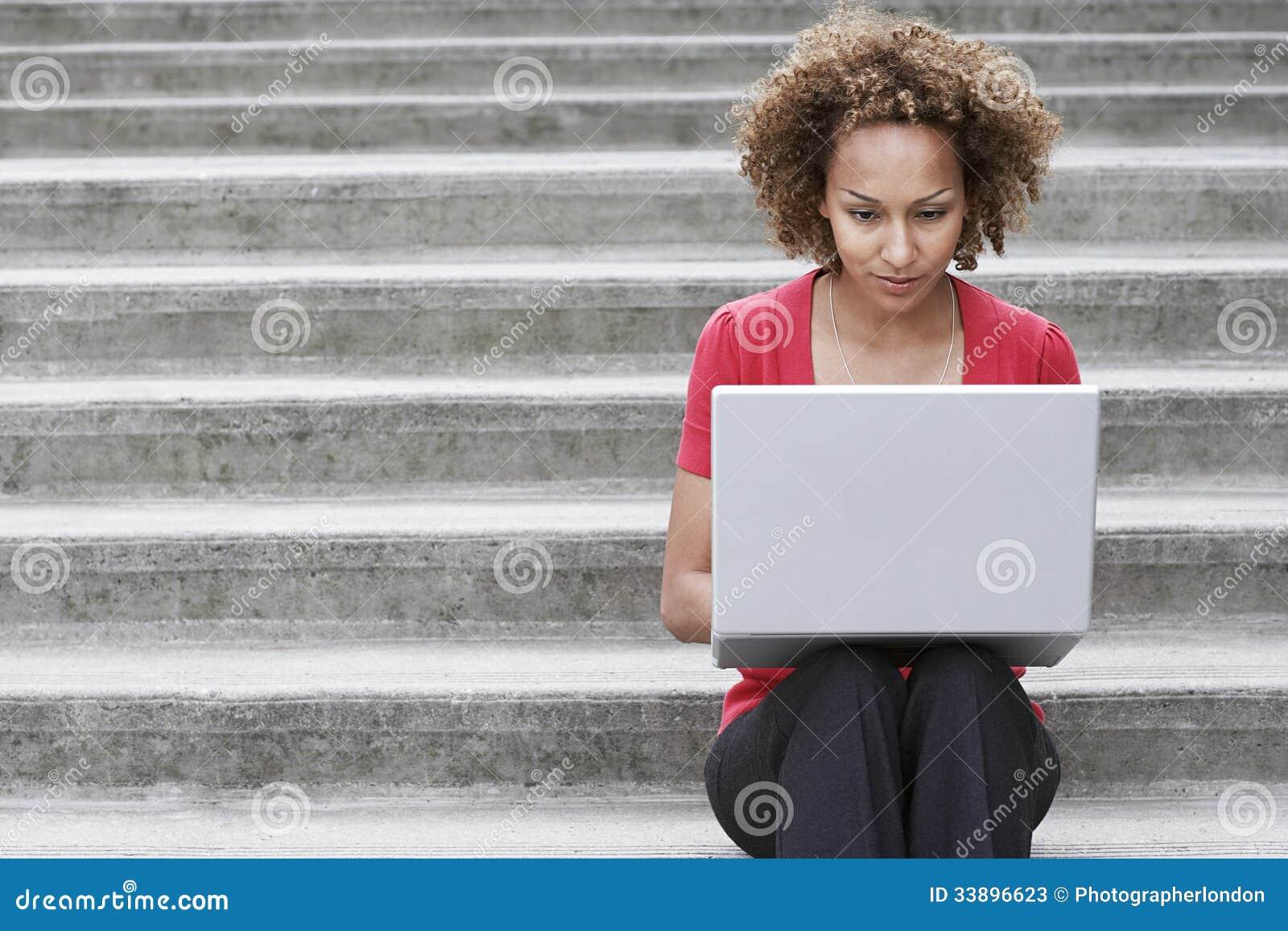 Mujer que usa el ordenador portátil en pasos al aire libre