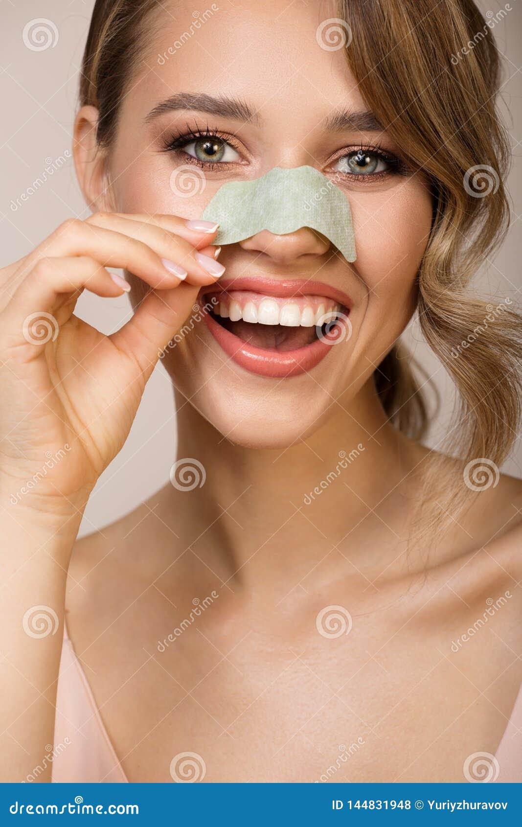 Mujer que usa la máscara del aplicador de la nariz