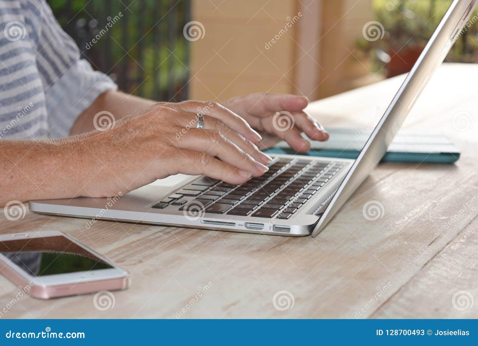 Mujer que usa la tecnología, un ordenador portátil, primer de manos