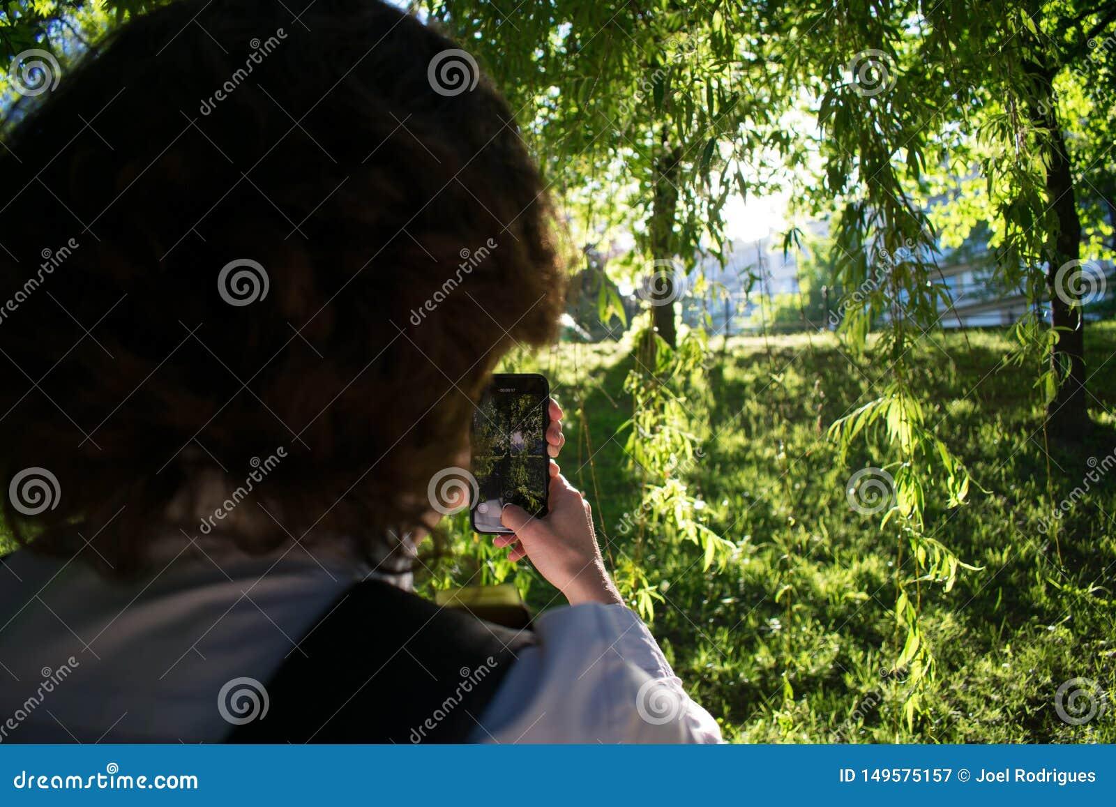 Mujer que usa smartphone para capturar puesta del sol hermosa en parque