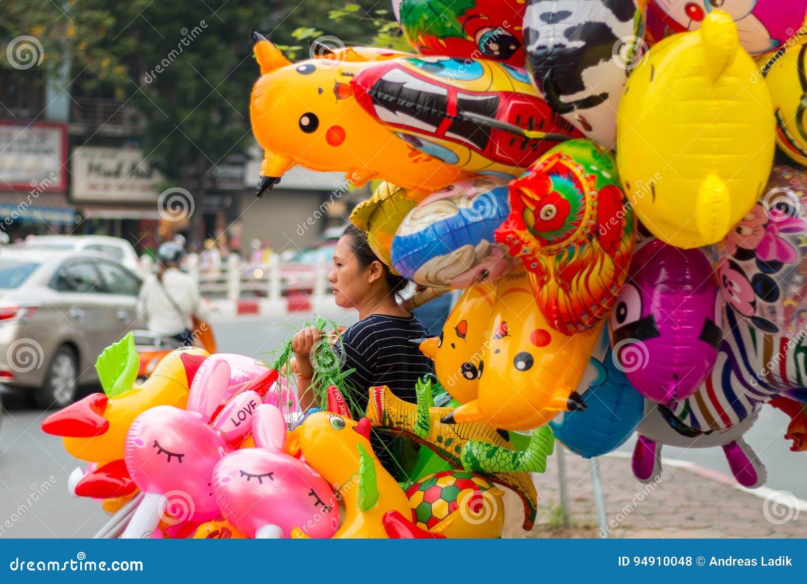 Mujer que vende los globos coloridos