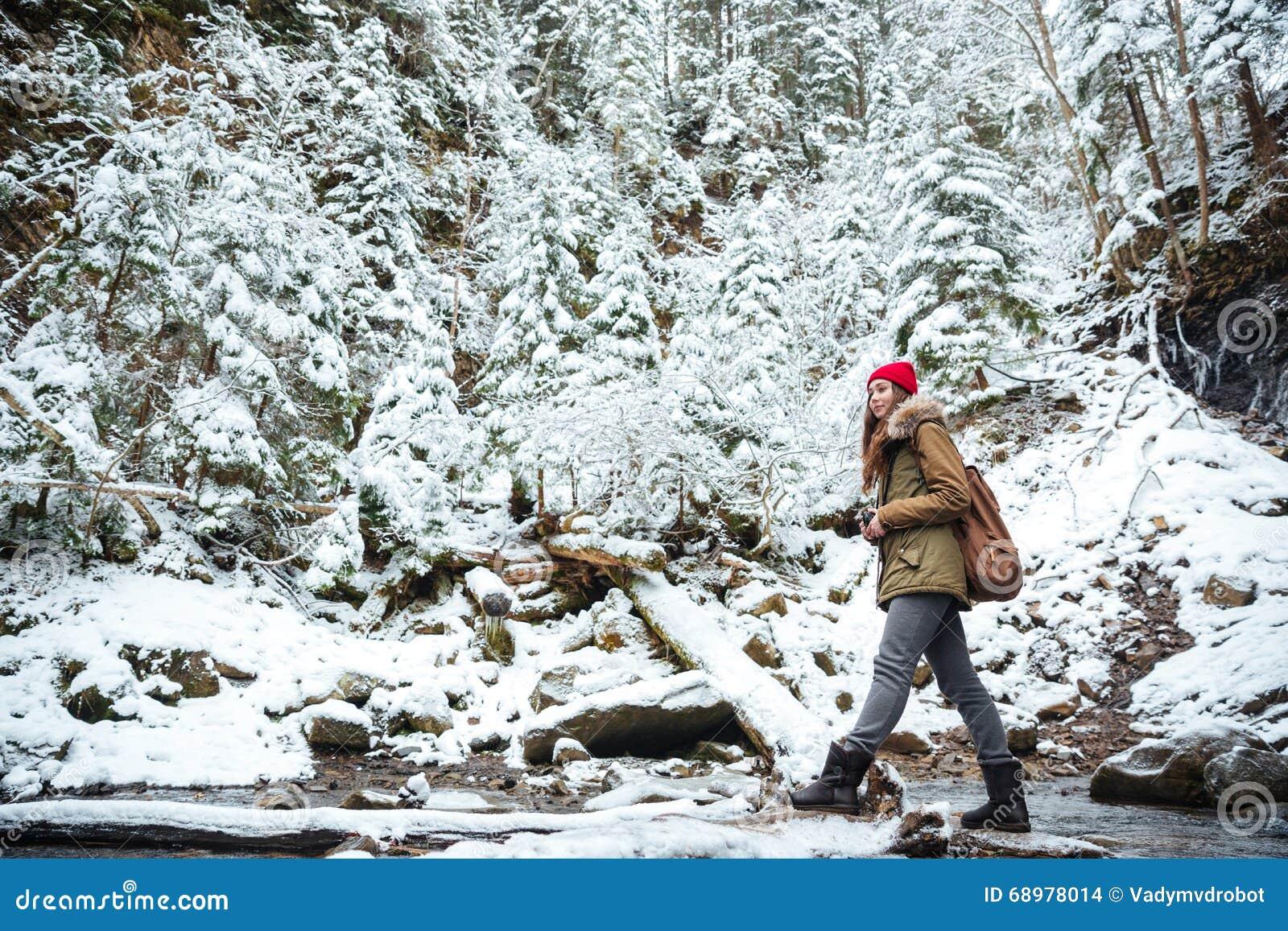 Mujer que viaja en bosque del invierno