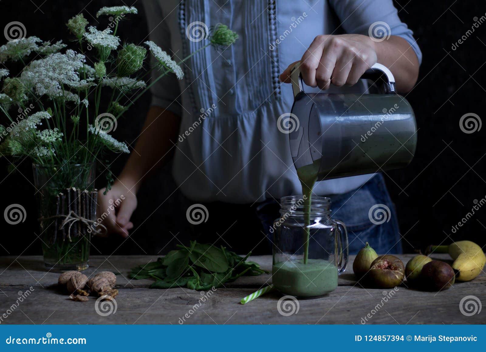 Mujer que vierte el smoothie verde recientemente mezclado en el tarro de cristal Prepa