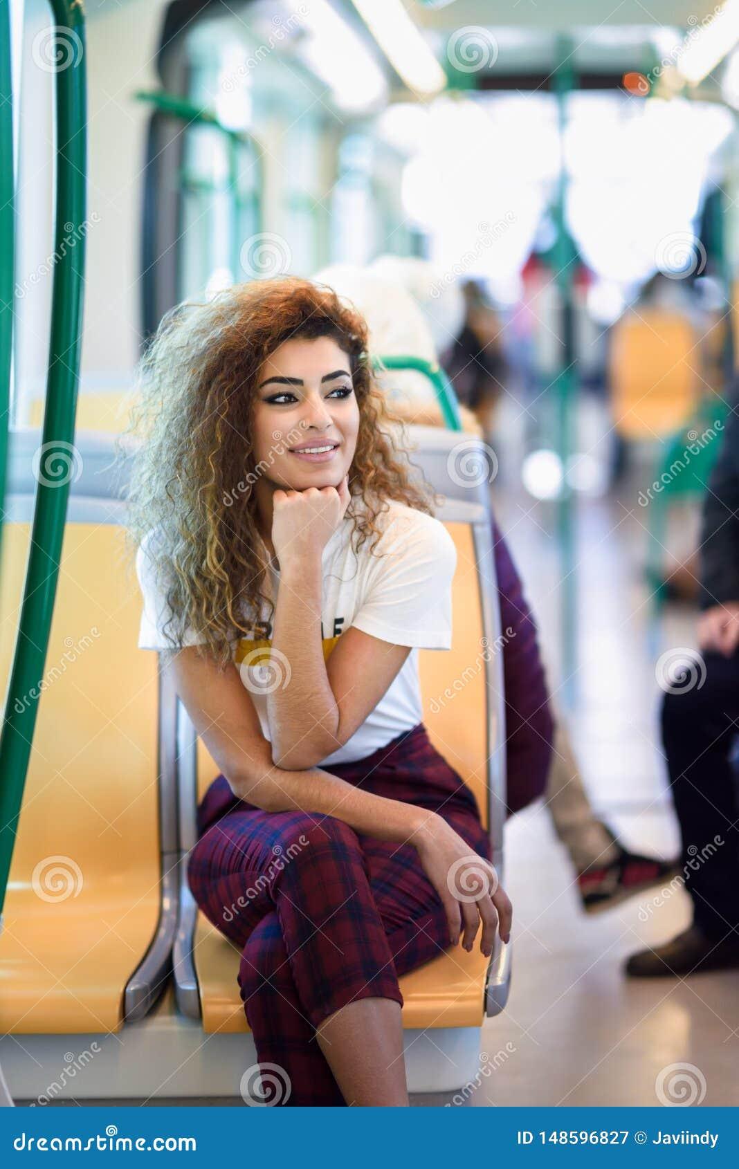 Mujer ?rabe dentro del tren del metro Muchacha ?rabe en ropa casual