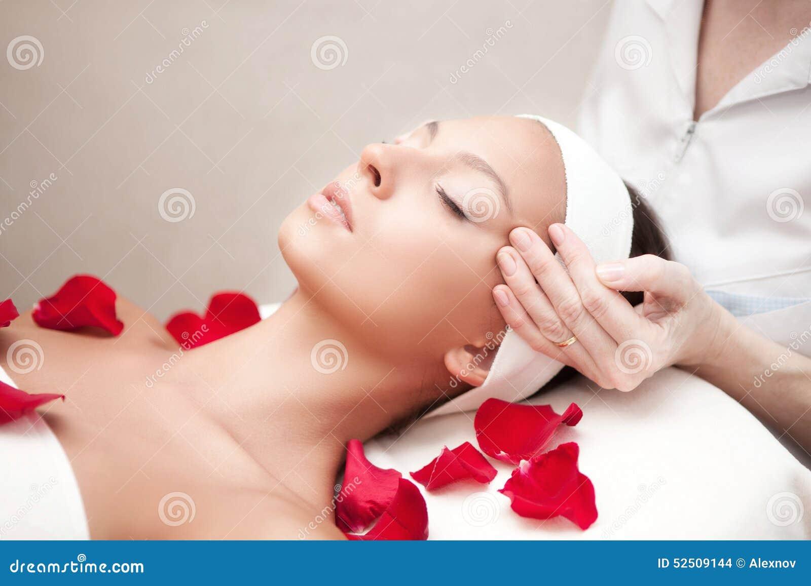Mujer relajante hermosa joven que tiene un masaje facial
