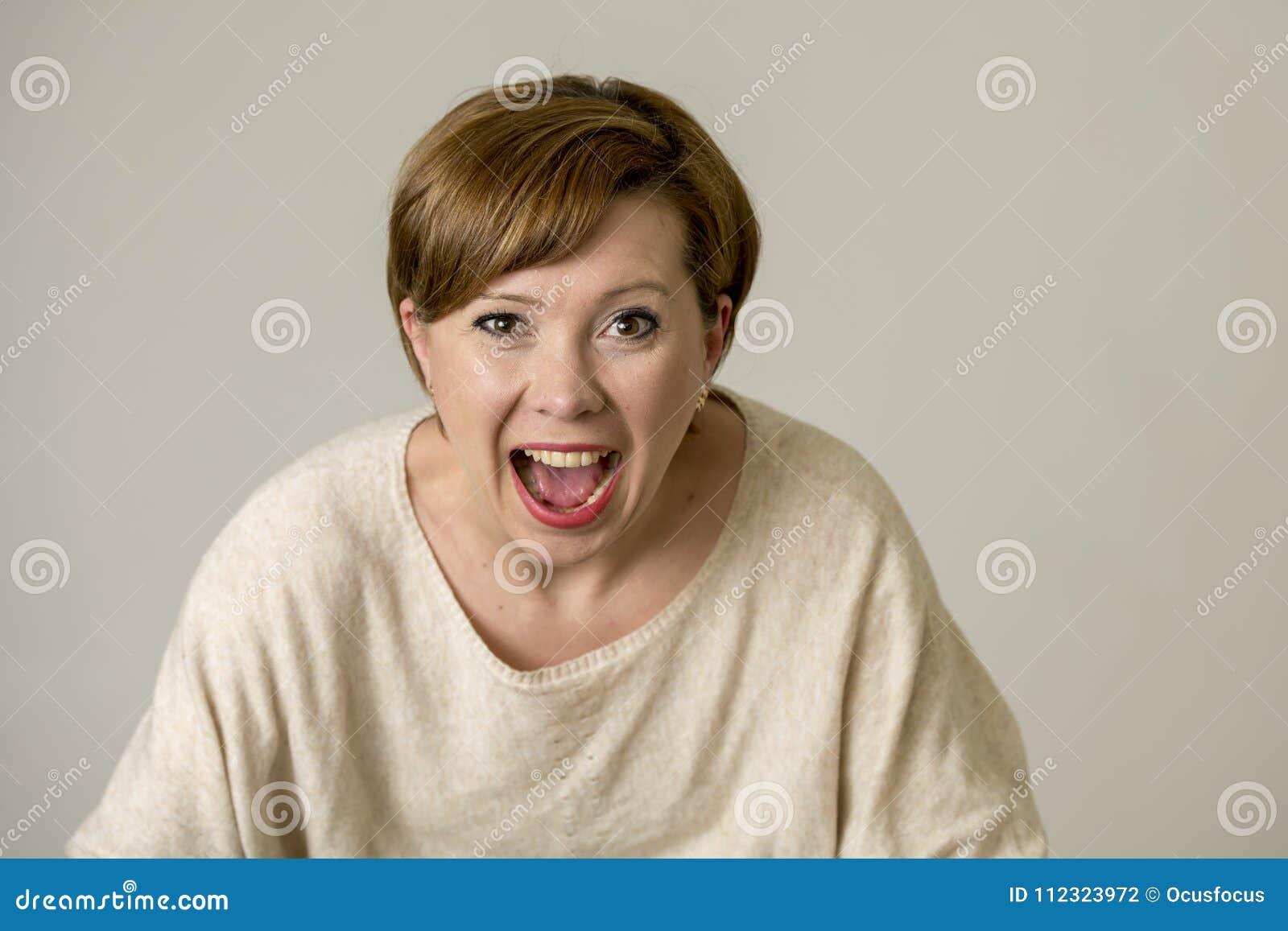 Mujer roja feliz y sorprendida joven del pelo que mira a la cámara encantada asombrosa y en la expresión de la cara de la sorpres