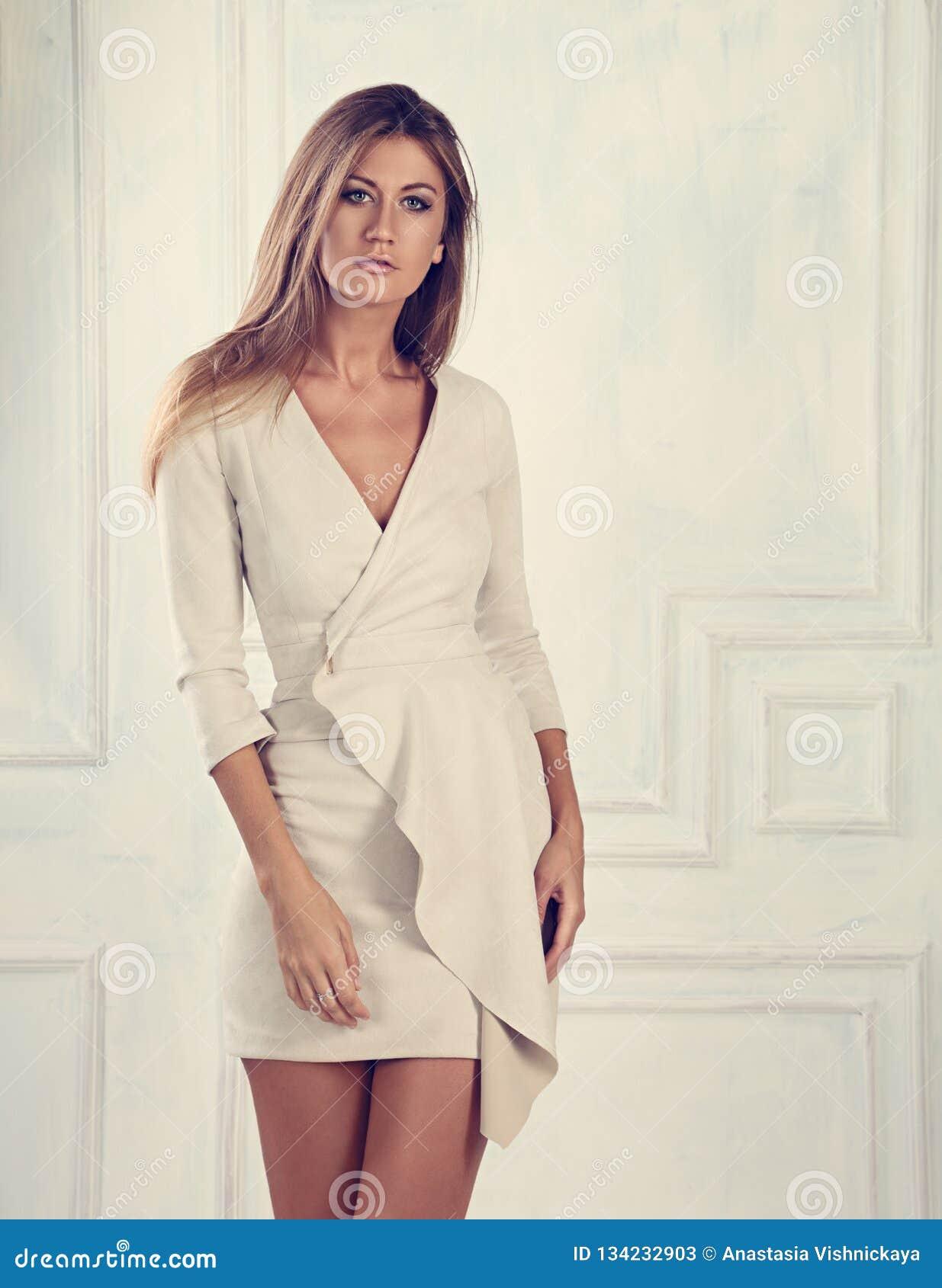 806e2e9df Mujer romántica hermosa con el pelo largo que presenta en vestido blanco  elegante de la moda