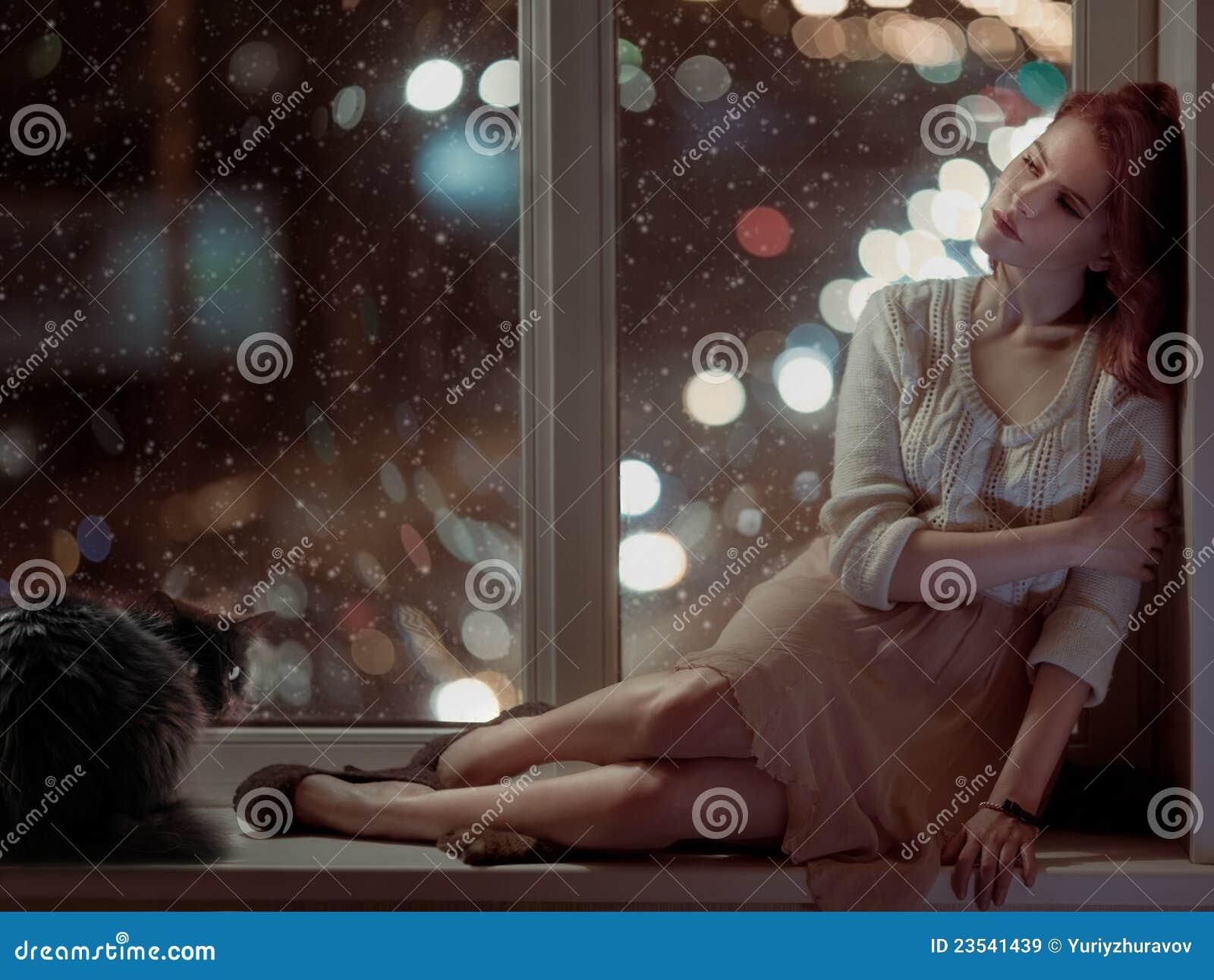 Mujer romántica y un gato que se sienta en una ventana