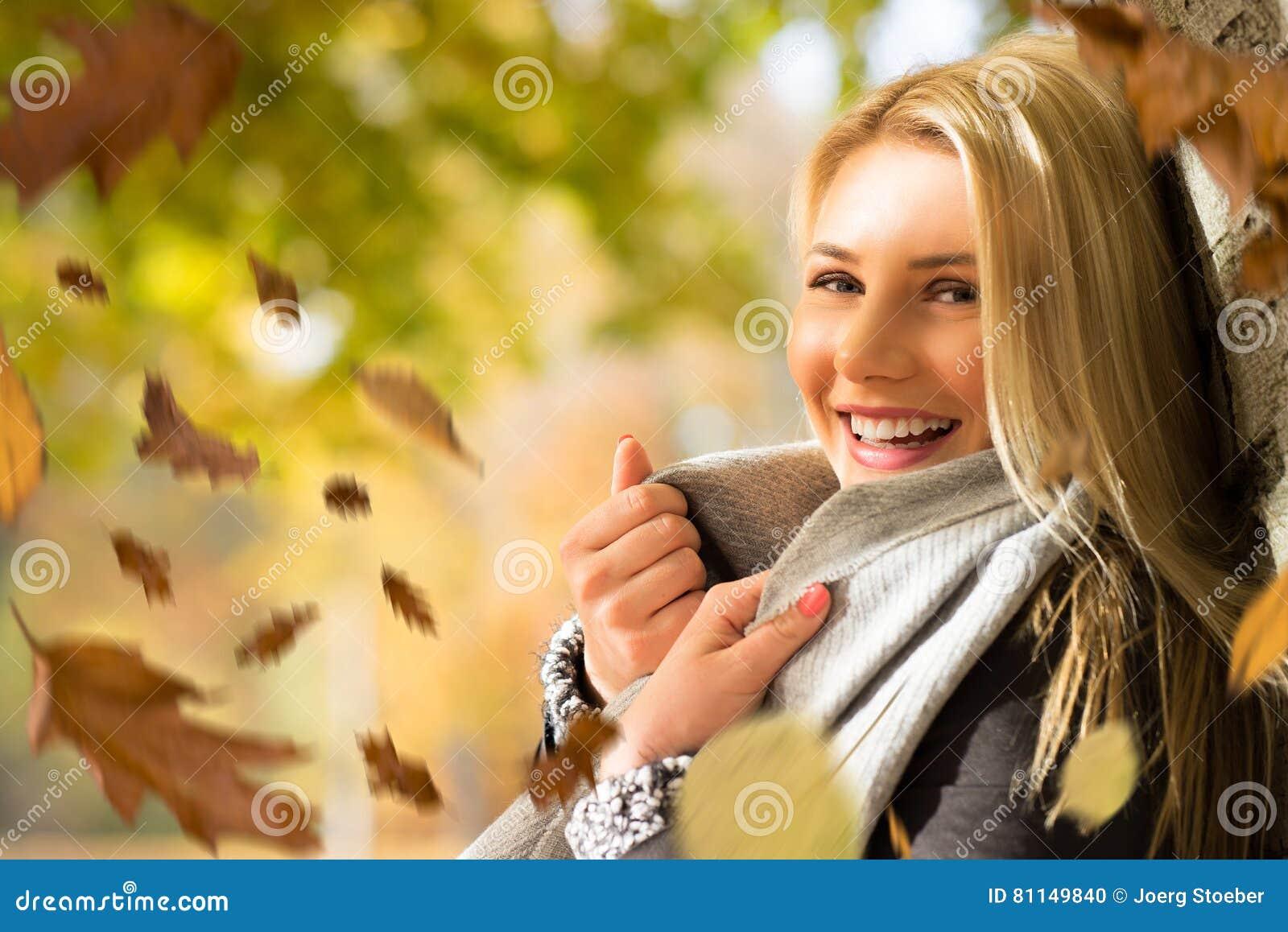 Mujer rubia atractiva en el sol del otoño