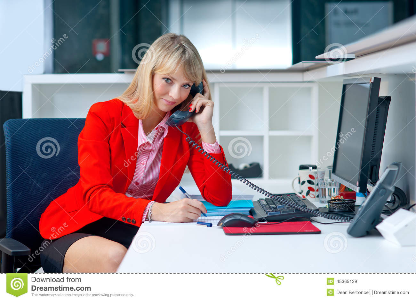 Mujer rubia atractiva en oficina que habla con el tel fono for Telefono de la oficina