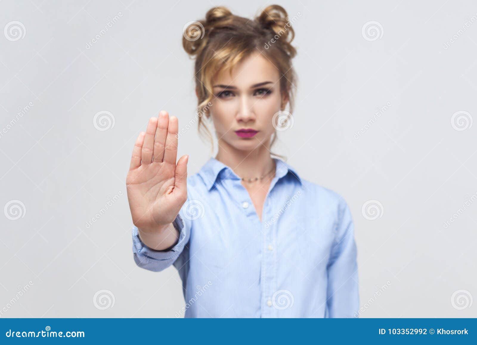Mujer rubia con la mala actitud que hace gesto de la parada con su palma
