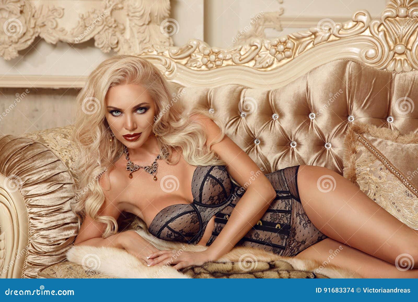 ec41faec0b5c Mujer rubia de fascinación hermosa en la lencería sexy que miente en el  sofá real en interior moderno de lujo Retrato de la foto del estilo de la  moda del ...