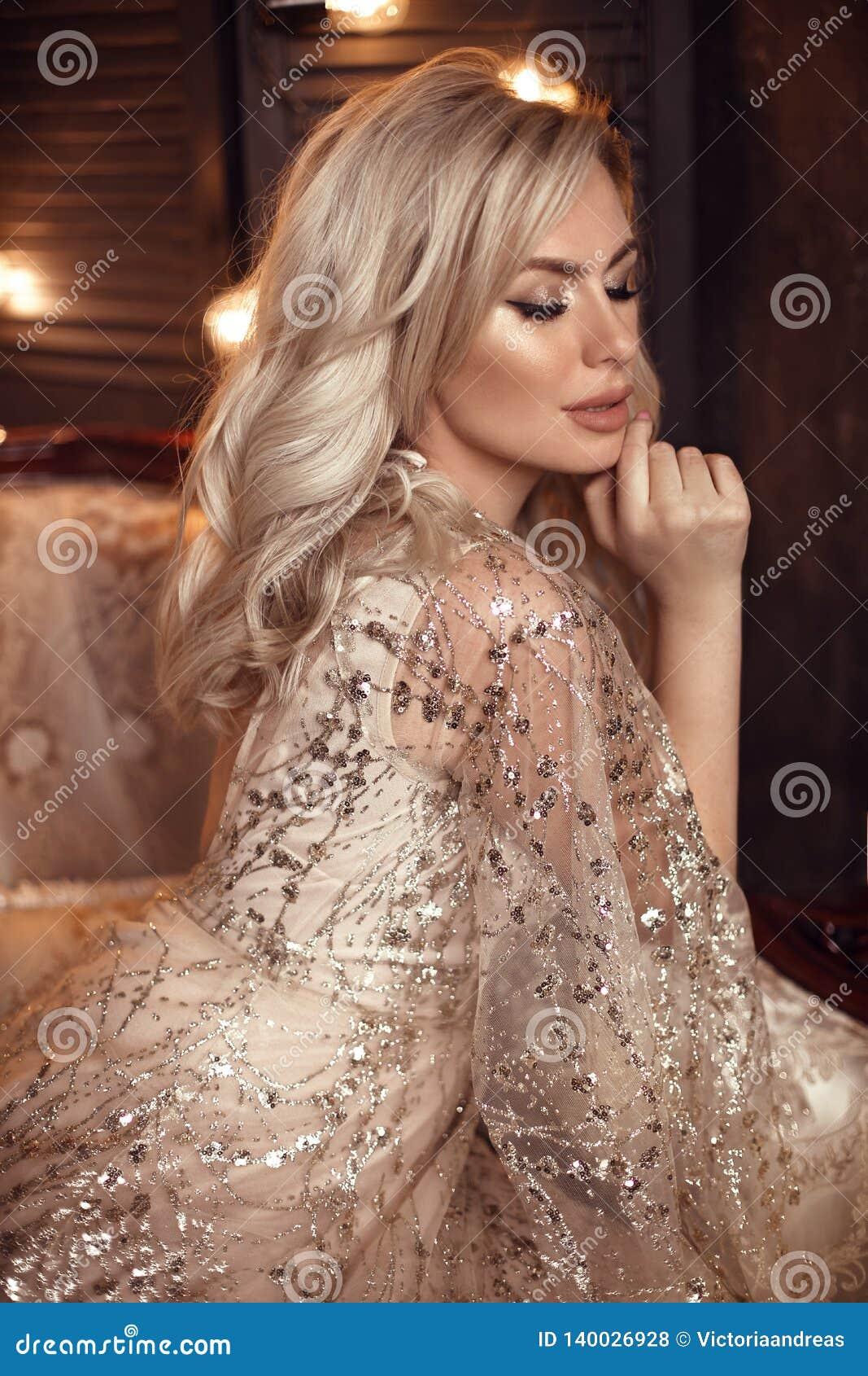 Mujer rubia elegante en el vestido beige que presenta en el sofá de lujo en interior real Novia sensual hermosa de la moda con el