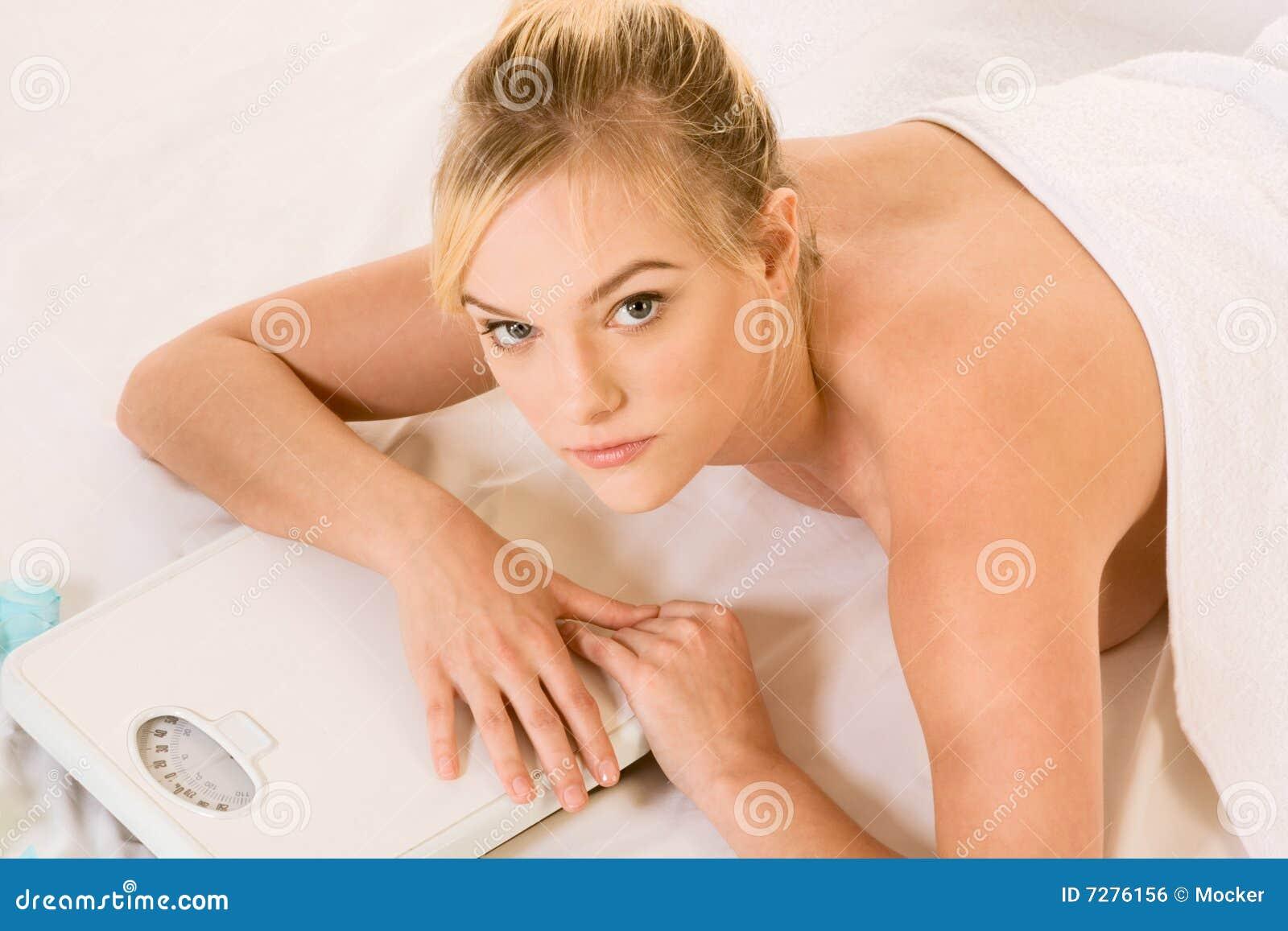 Mujer rubia en el balneario que sostiene encendido escalas del peso