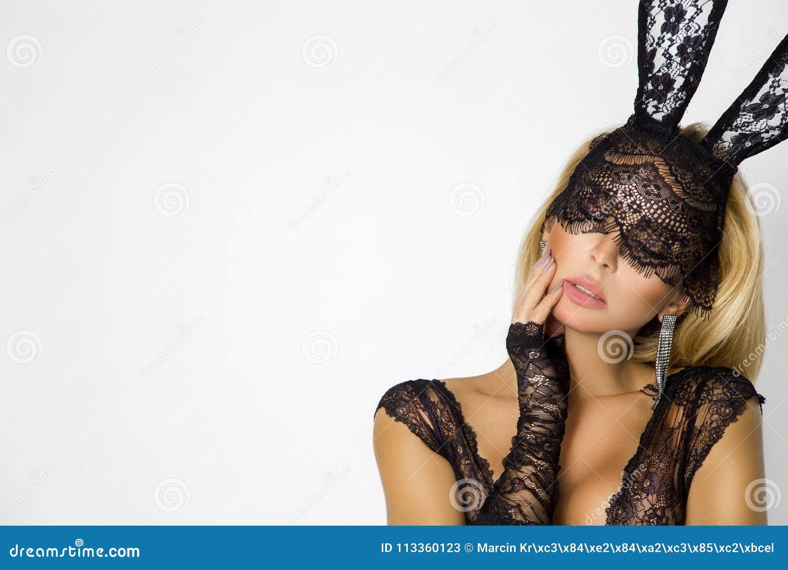 Mujer rubia hermosa, atractiva en ropa interior elegante y máscara negra del conejito de pascua del cordón
