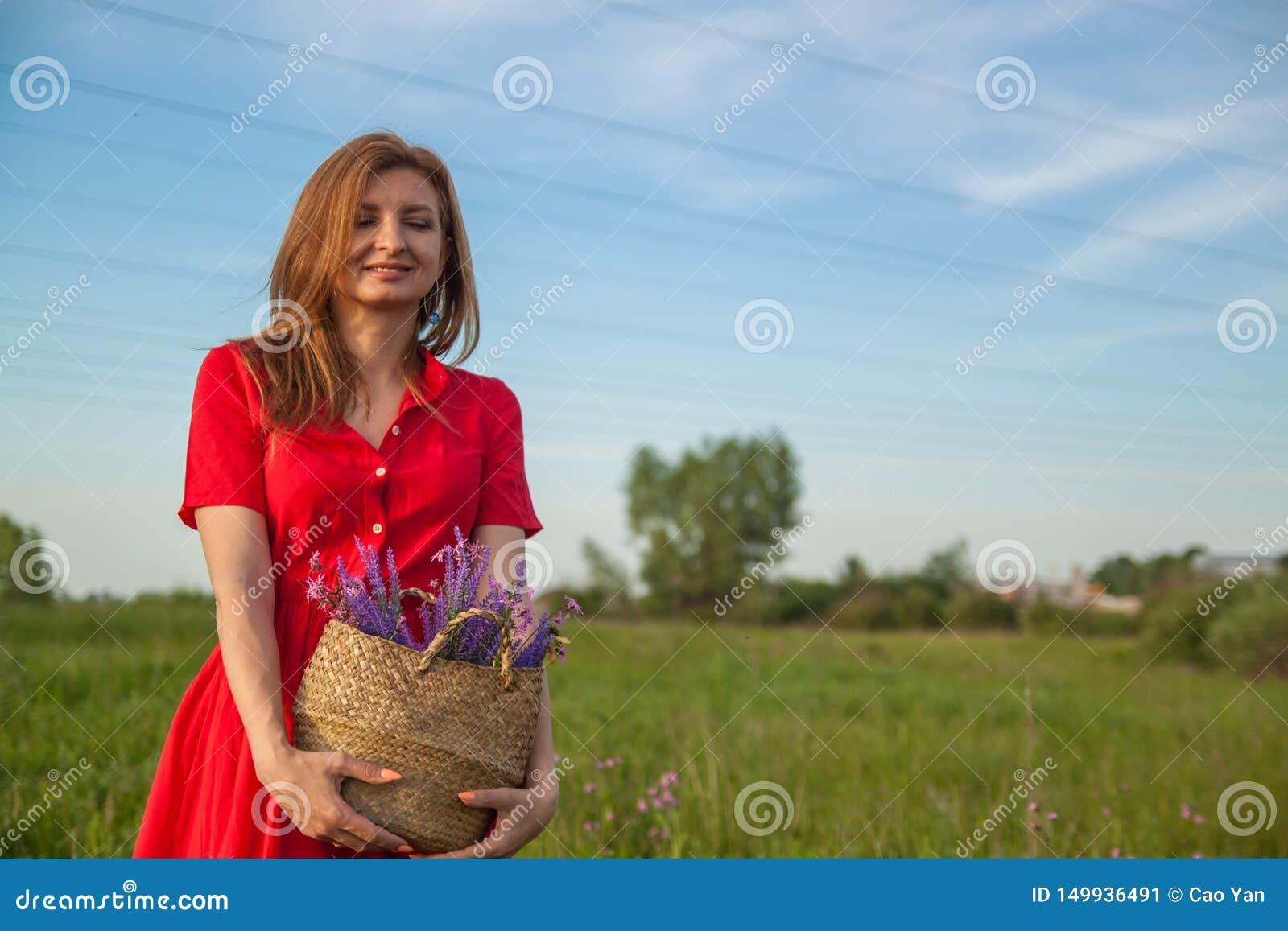 Mujer rubia hermosa joven smilling con las flores en naturaleza en el verano
