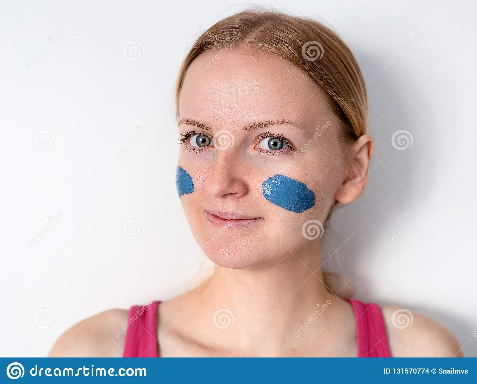 Mujer rubia hermosa que hace que la máscara facial de la arcilla azul se aplique por el cosmetólogo la muchacha con una máscara e