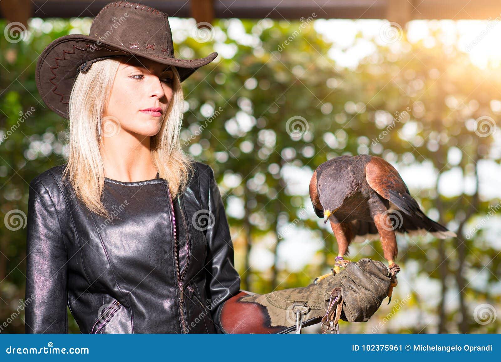 Mujer rubia hermosa que sostiene un halcón de harris en un glo protector