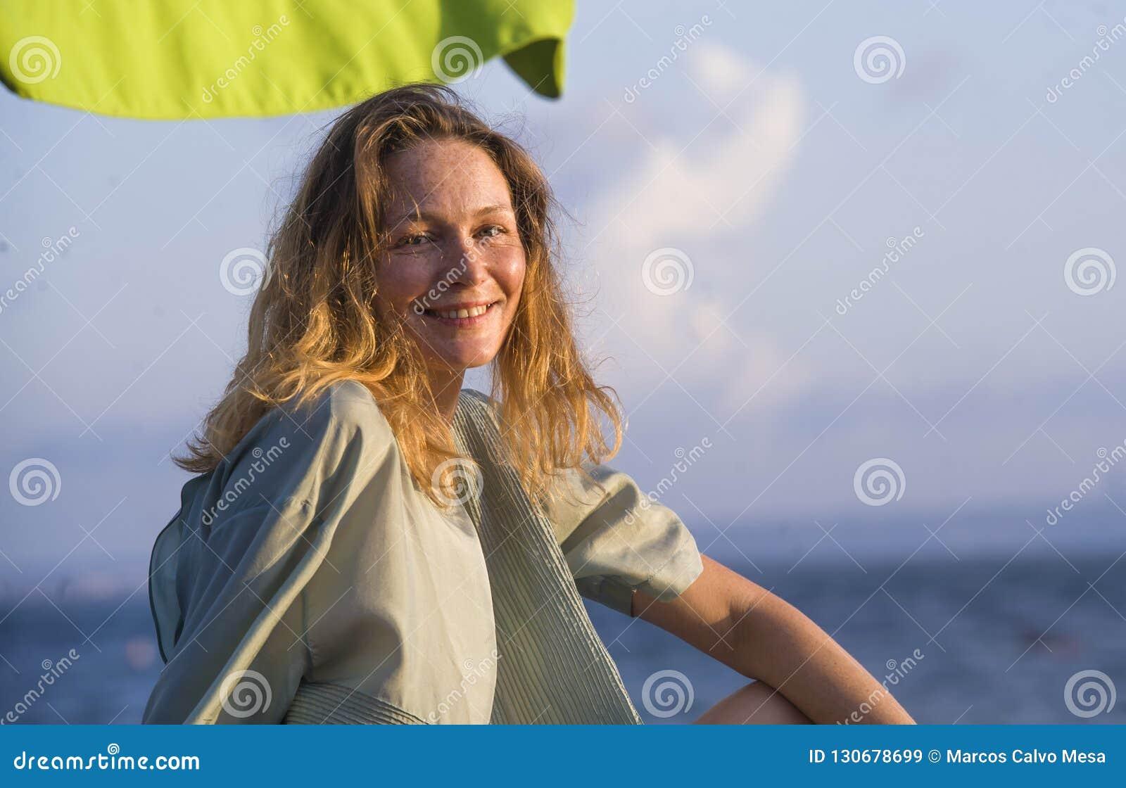 Mujer rubia hermosa y atractiva feliz joven que presenta en la playa bajo sonrisa del paraguas pensativa mirando el mar despreocu