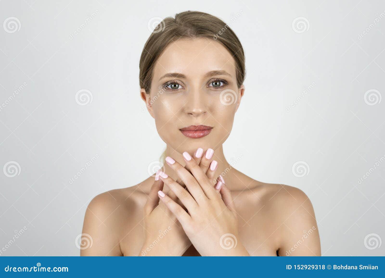 Mujer rubia joven atractiva que pone una mano en otras manos que se sostienen cerca de cierre de la barbilla encima del fondo bla