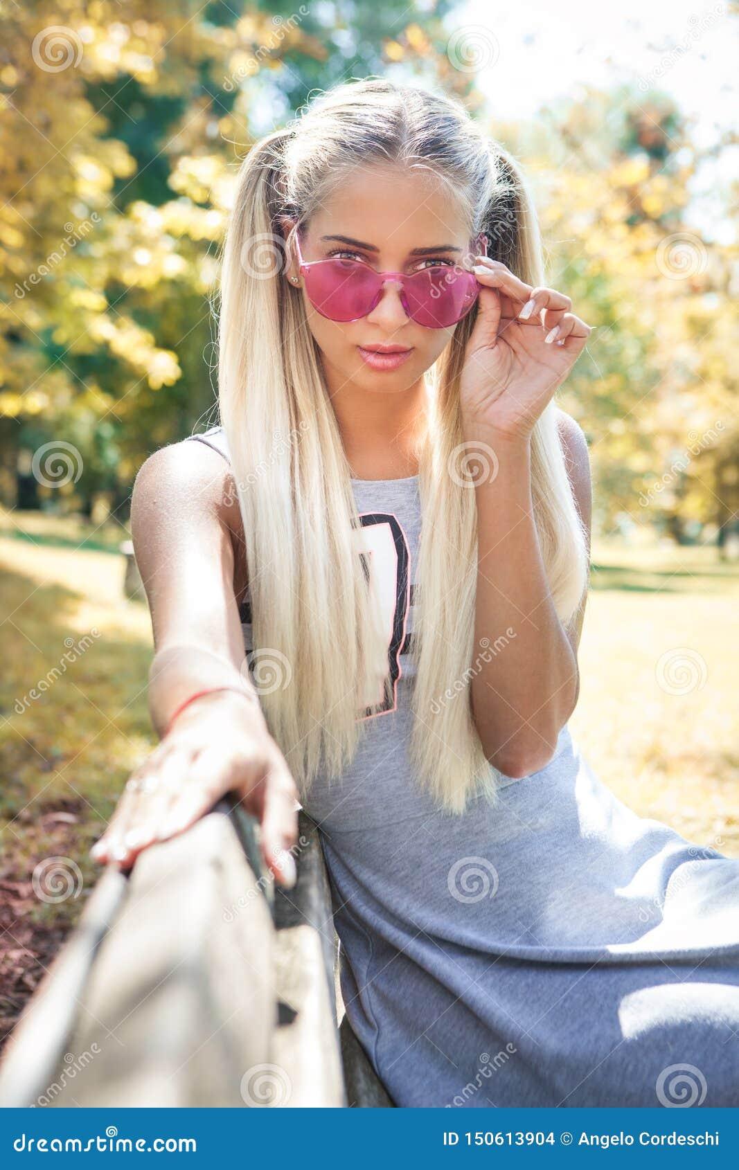 Mujer rubia joven con las gafas de sol coloridas que se sientan en un banco al aire libre