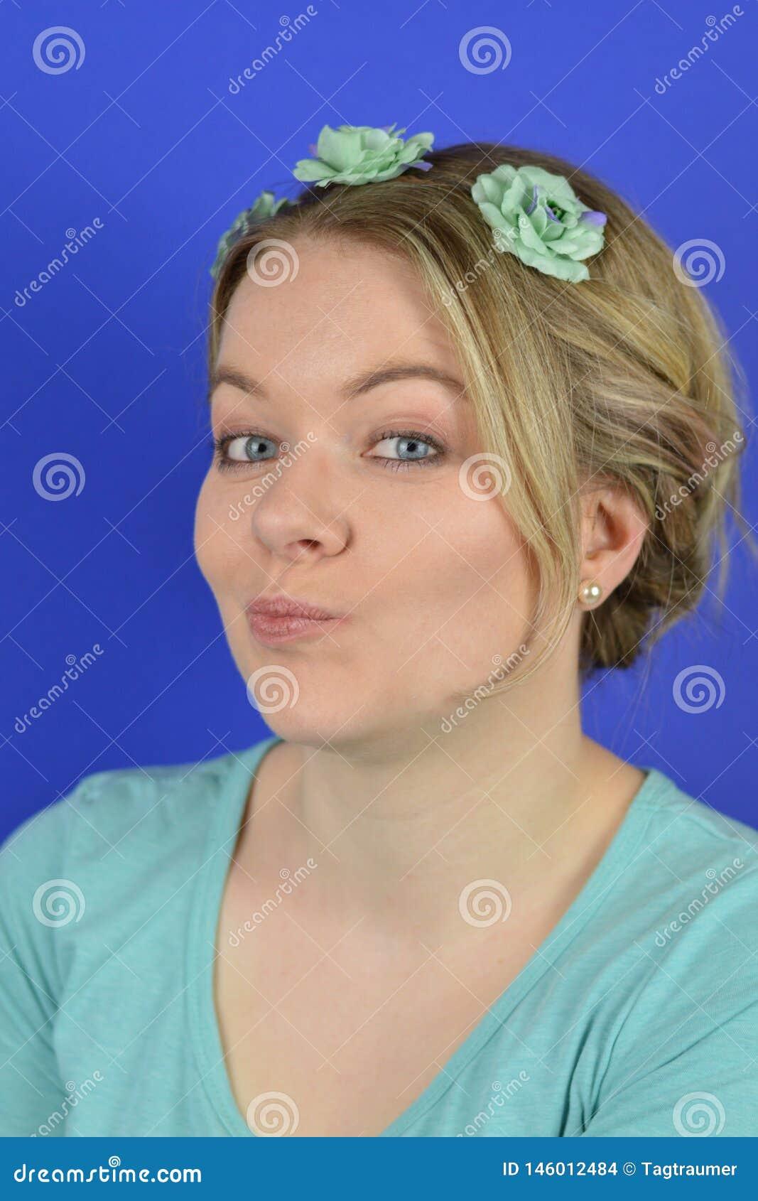 Mujer rubia joven escéptica con las flores en un anillo del pelo