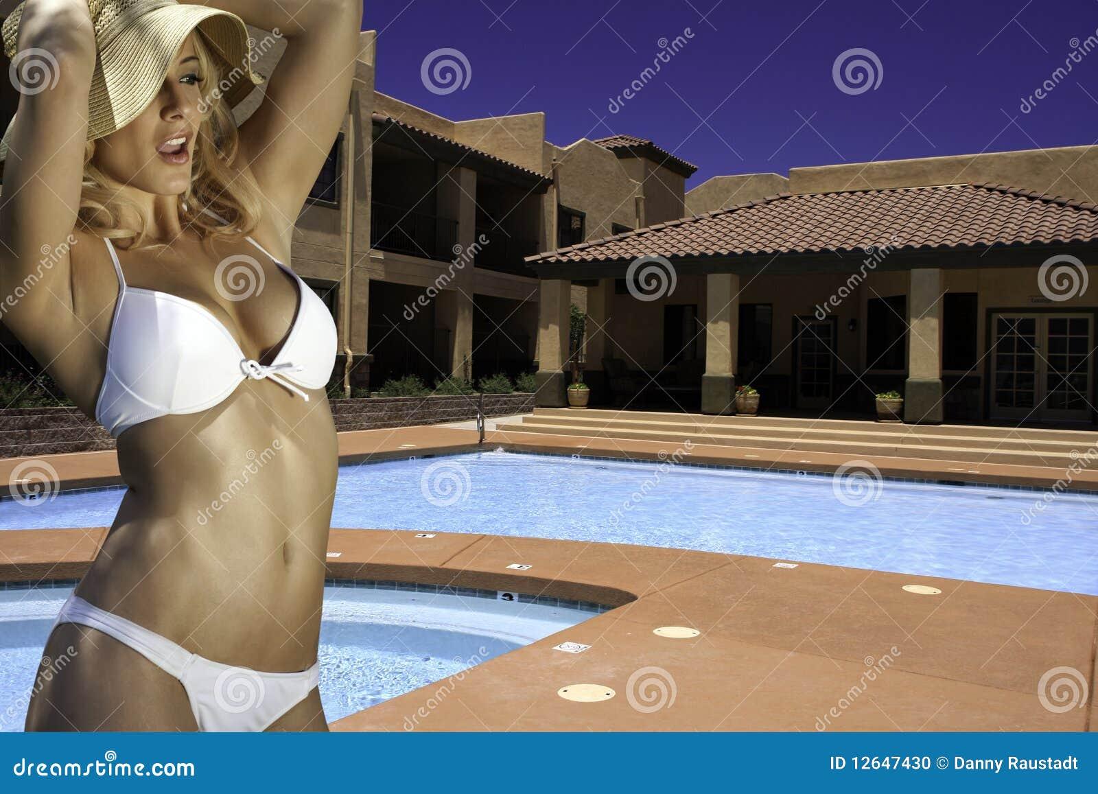 Mujer rubia joven hermosa en la piscina del hotel de centro turístico