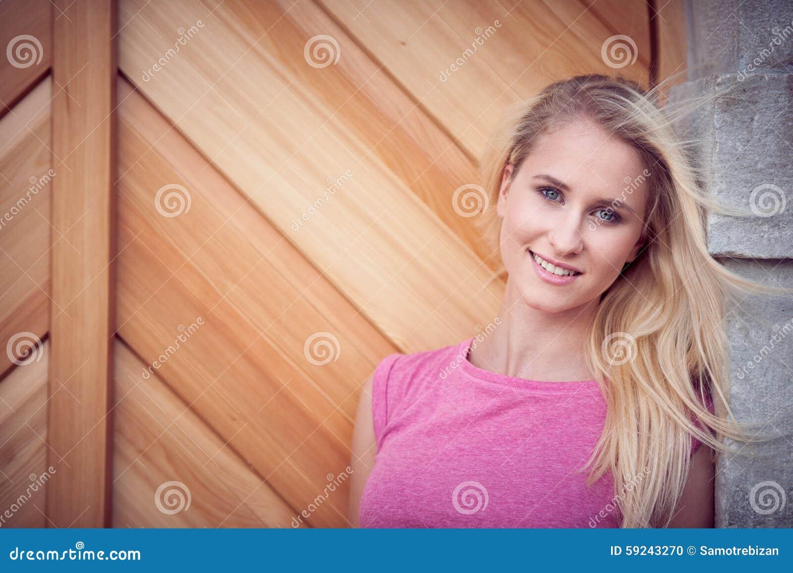 Mujer rubia joven hermosa en un arownd del paseo la ciudad cerca al castillo en día soleado del verano