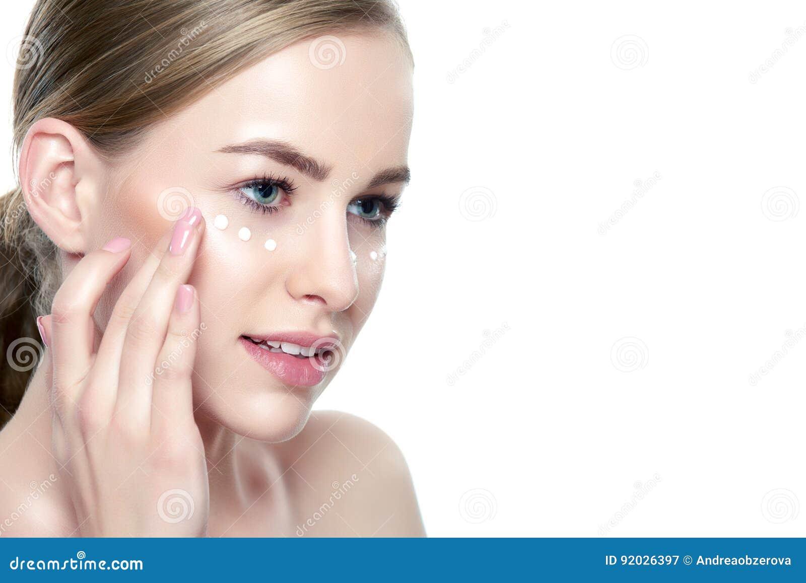 Mujer rubia joven hermosa que aplica la crema de cara debajo de ella ojos Tratamiento facial Cosmetología, belleza y concepto del