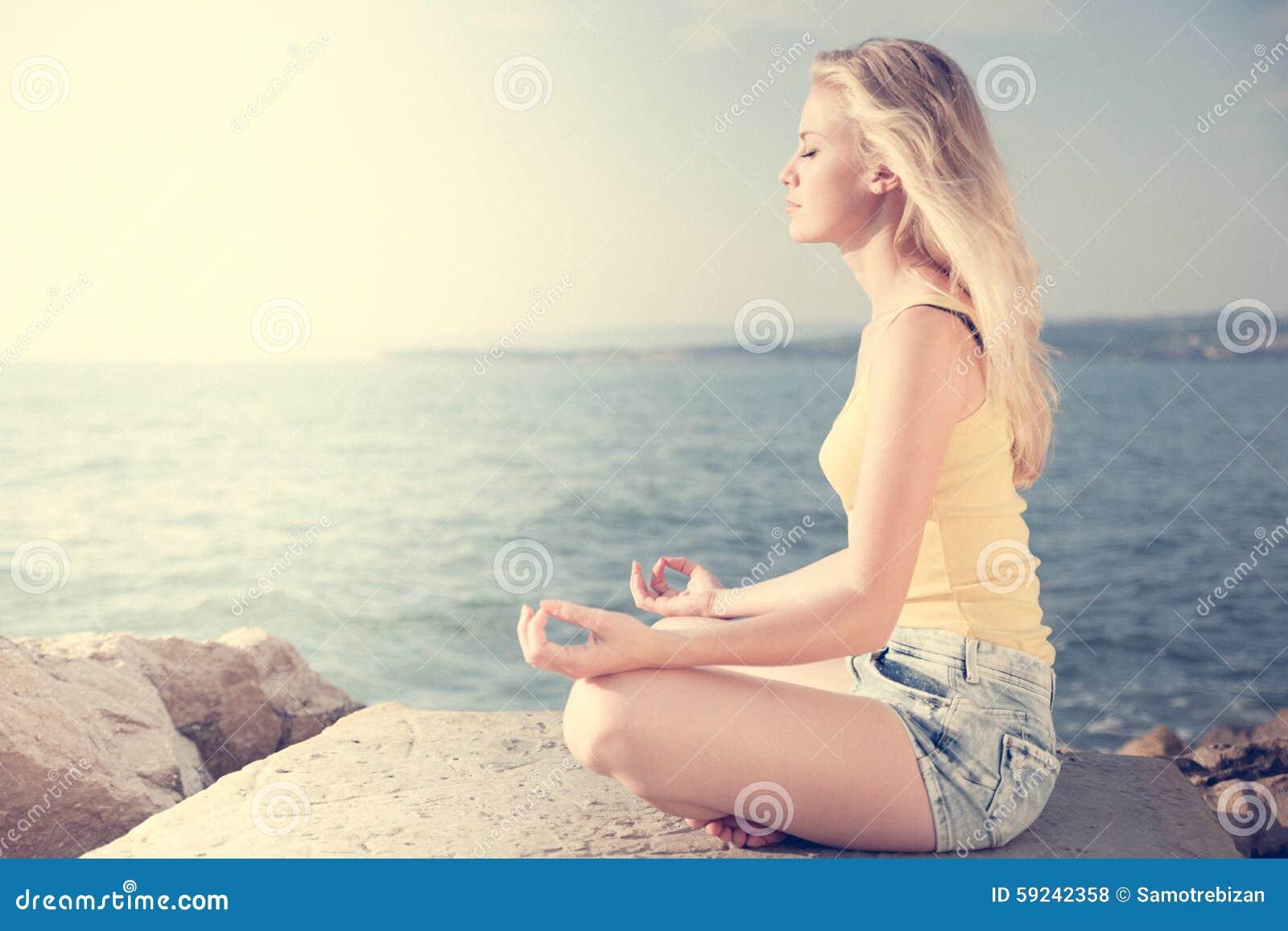 Mujer rubia joven hermosa que reflexiona sobre una playa en la salida del sol adentro